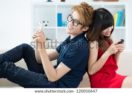 Young people sitting back to back with mobile phones