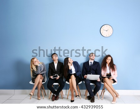 Shutterstock Young people sitting on a chairs and looking at the clock in blue hall