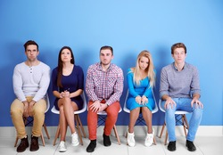 Young people sitting on a chairs in blue hall