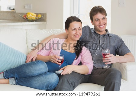 Young people sitting on the couch while watching television in the living room