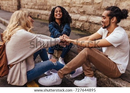 Young people sitting together and holding their hands in joy. Friends with their hands stacked showing unity and teamwork. #727644895