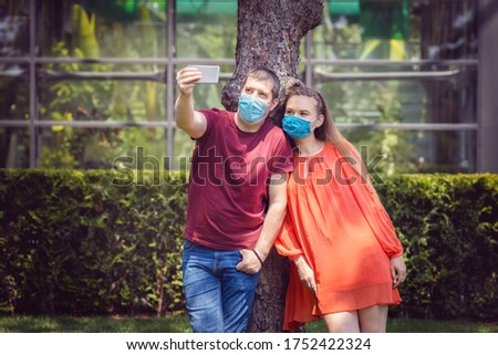 Young people taking selfie outdoor wearing protective face masks – New normal life concept with happy couple having fun in weekend after lockdown reopening sharing photo on social media staying safe