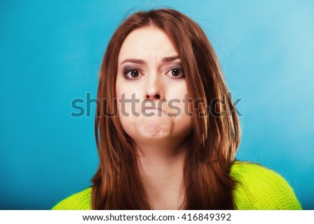 Young people teenage concept - funny girl making silly face, unhappy face expression on blue