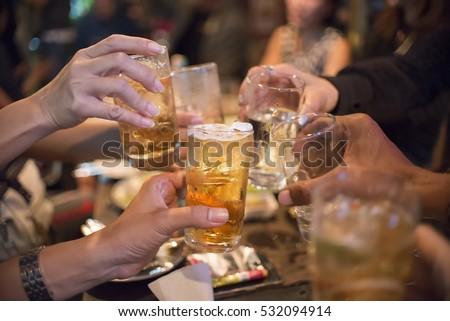 Young People toasting and cheer beer glasses,drink at bar party.Happy hour or chill out time,group of friends (female and men)drunk beverage(beer,wine,cocktails) .Birthday,celebrate party concept.