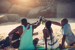 Young people toasting with beer bottles while sitting on beach. Group of friends having drinks together.