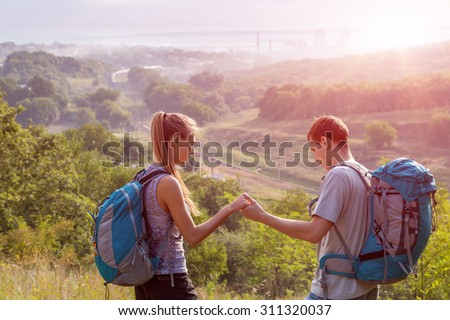 Young People Traveling.\ Girlfriend and Boyfriend Teenagers Couple with Backpacks on Green Forest Background Holding Hands Talking Smiling rising Sun on Background