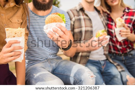 Young people walking outdoors. Sitting in the park and eat fast food