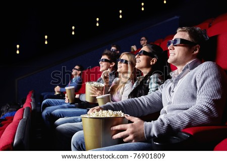Young people watch movies in cinema - stock photo