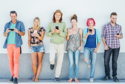Young people watching on their smart mobile phones leaning on a wall - Generation addicted to new technology - Concept of youth addiction to social network trends
