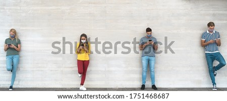 Young people wearing face mask using mobile phone keeping social distance - Millennial friends watching media trends on smartphones during corona virus outbreak - Youth and technology concept Foto stock ©