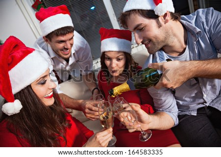 Young people wearing Santa\'s hats drinking champagne on new year\'s eve.