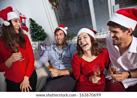 Young people wearing Santa\'s hats having a toast with champagne on new year\'s eve.