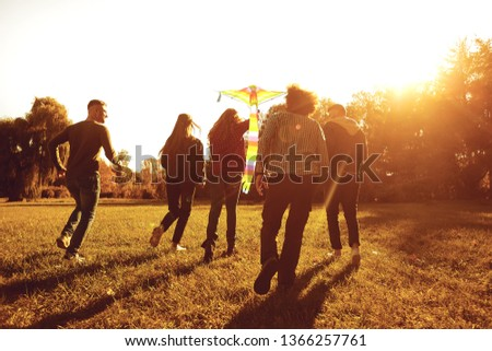 Young people with a kite run on the grass in the park. #1366257761