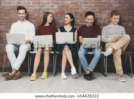 Young people with gadgets sitting on chairs - Shutterstock ID 654478222