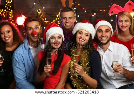 Young people with glasses of champagne at Christmas party