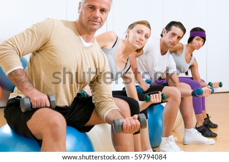 Young people with instructor lifting weights on a fitness ball at gym