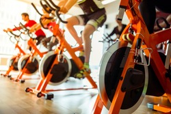 Young people working out on an exercise bike in gym, close-up