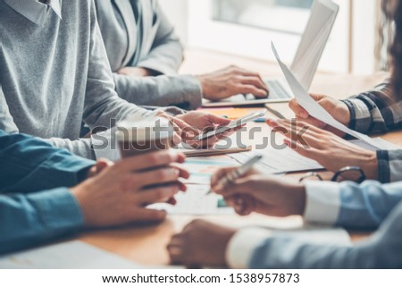 Young people working together at office having business meeting table close-up browsing digital devices drinking hot coffee taking notes Stockfoto ©
