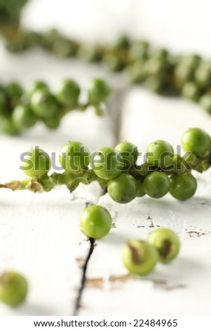 young peppercorn, closeup green seed, on wooden background.