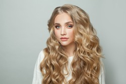 Young perfect woman blonde model with with curly hairstyle on white background