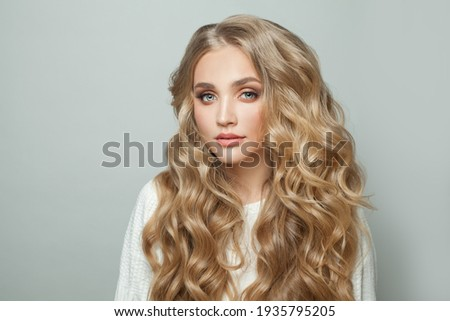 Young perfect woman blonde model with with curly hairstyle on white background Foto stock ©