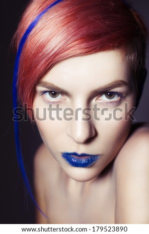 Young person with blue lips, blue ears and pink hair with blue strand on it looking at camera. Blue background