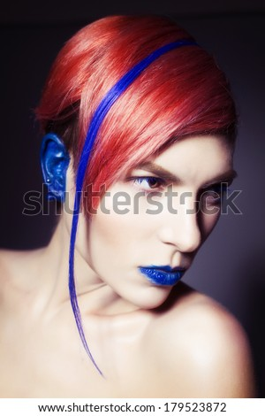 Young person with blue lips, blue ears and pink hair with blue strand on it looking forward. Blue background