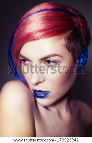 Young person with blue lips, blue ears and pink hair with blue strand on it looking sideways. Blue background