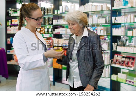 Young pharmacist giving advices about medication to senior female patient in a pharmacy