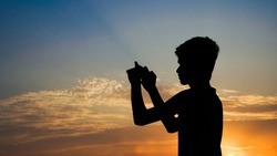 Young phone photographer capturing the sunset