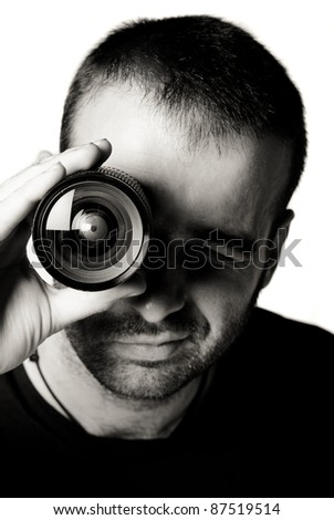 Young photgrapher holding a lens in his eye