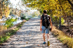 Young photographer man back walking on trail path road during autumn Potomac river in Great Falls, Maryland with colorful foliage and backpack tripod