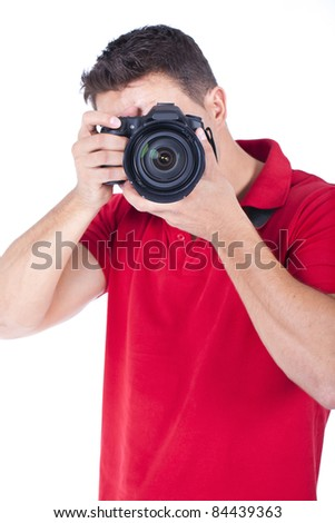 young photographer standing and shooting with his camera - stock photo