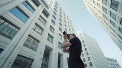 Young photographer takes picture of modern urban architecture. Action. Bottom view of guy photographing modern architecture with camera. Photographer shoots office buildings against blue sky