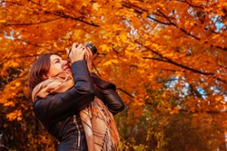 Young photographer takes pictures of autumn forest at sunset