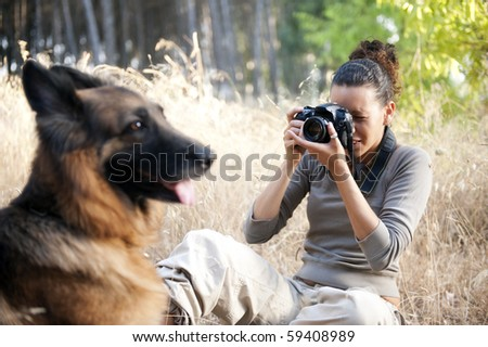 Young photographer taking a photo of her dog - stock photo