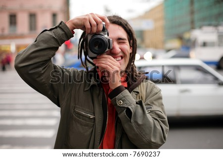 Young photographer taking a photo with DSLR camera