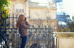 Young photographer taking picture of the Eiffel tower