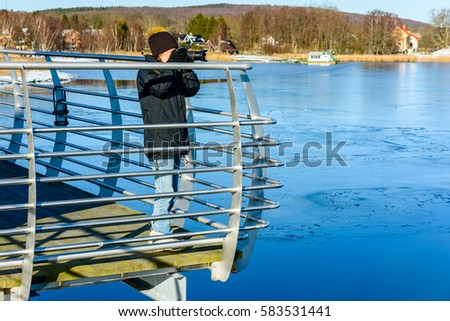 Young photographer taking picture while standing on bridge with icy water down below. Cold but sunny day in early spring or winter. Landscape in background. #583531441