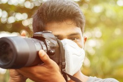 Young photographer with Pollution mask - Concept of Photojournalism and its risk.