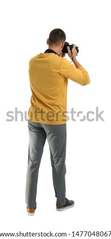 Young photographer with professional camera on white background, back view