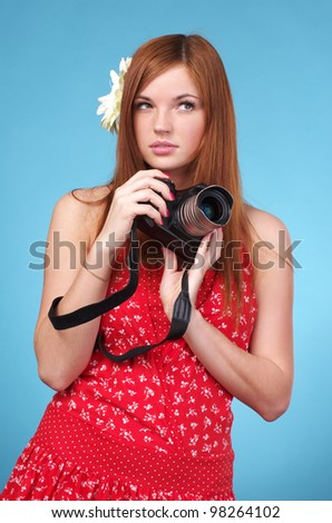 Young photographer woman holding camera against blue background