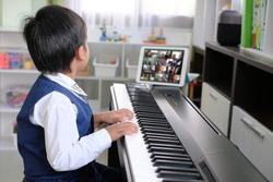 Young pianist boy looking at the digital tablet screen for learning piano online at home. Music distance learning concept.