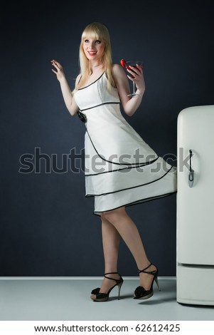Young pin-up sexy girl with white mini dress jammed fridge door