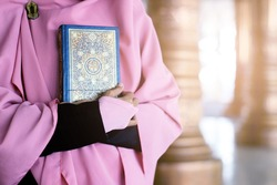 Young Pious Beautiful Muslimah Woman Wearing Pink Veil In The Mosque - Holding & Hugging The Holy Book Of Quran As Islamic Religion Basic Universal Knowledge Source