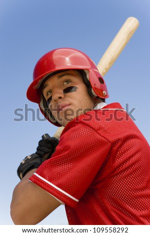 Young player ready to hit a shot against clear sky
