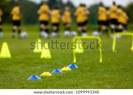 Young Players at the Football Training Session. Young Footballers Training Run with Ball DrillsSoccer Balls, Pylons, Cones, Marks and Training Hurdles on Grass Pitch. Youth Soccer Pre-season Training