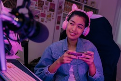 Young playful Asian woman sitting in front of her computer workstation and smiling at the screen with a microphone in foreground. Beautiful asian woman working from her home studio and playing game.