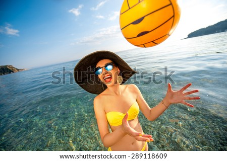 Young playful woman standing in the water with yellow ball on the beach. Summer water game concept