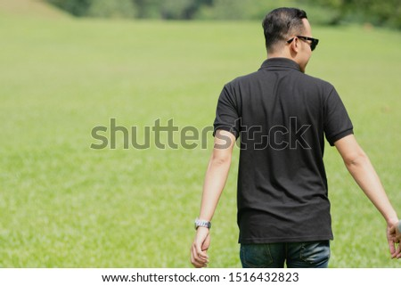 Young playful young muslim Asian couple  running together hand by hand on natural background or a  summer field
